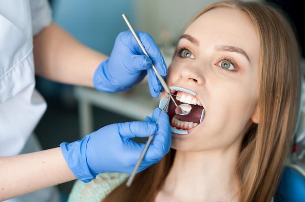 歯科医は歯科医院で患者の歯を調べます。