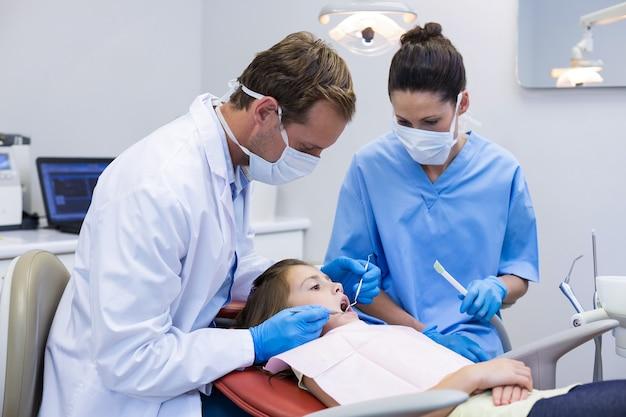 Стоматолог осматривает молодого пациента с инструментами