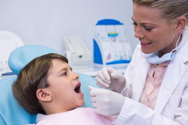 診療所で男の子を診察する歯科医