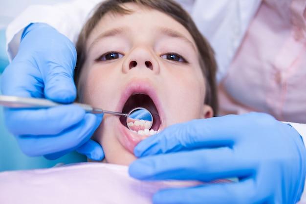 クリニックでかわいい男の子を調べる歯科医