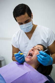 Dentist examining female patient teeth