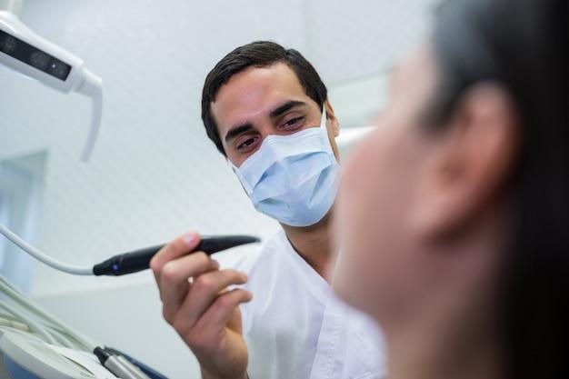 Dentist examining female patient