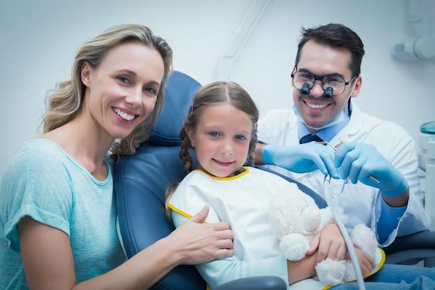 アシスタントと女の子の歯を調べる歯科医