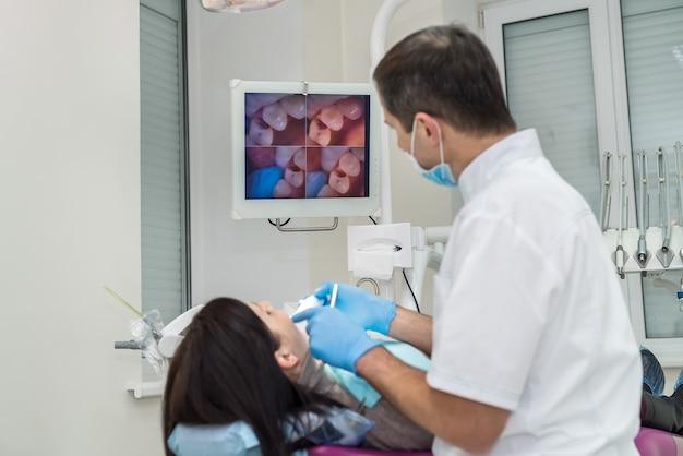 Dentist examining patient's teeth with oral camera