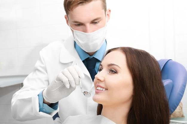 Стоматолог, исследующий зубы пациента в клинике