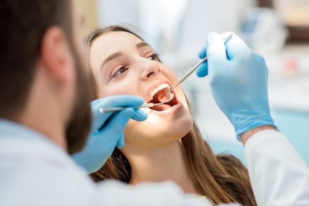 歯科医は、マウスミラーと歯科用掘削機で患者の歯を検査します。女性の顔のクローズアップビュー