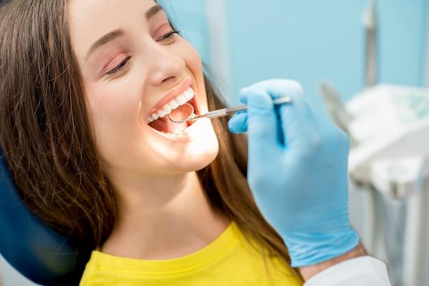 歯科医がマウスミラーで患者の歯を調べます。女性の顔のクローズアップビュー