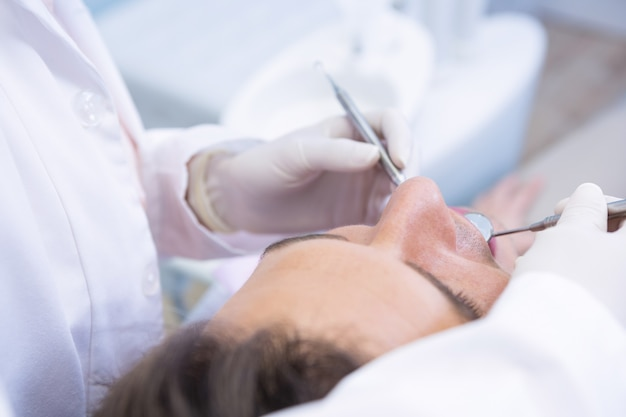 Dentist giving dental treatment to man at clinic