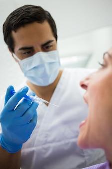 メスの患者に注射を与える歯科医