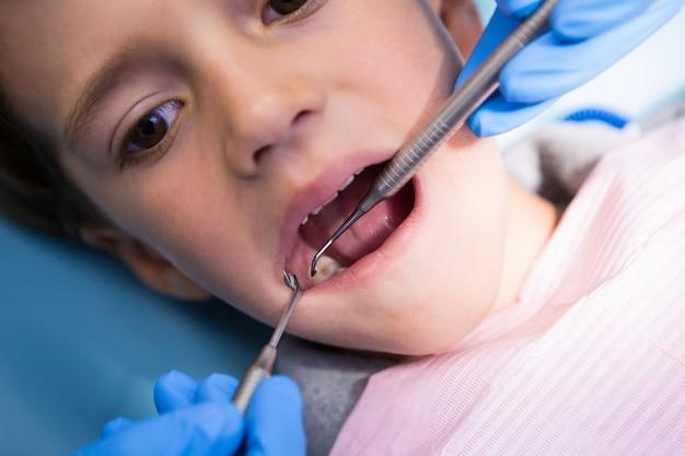 診療所で男の子に治療をしている歯科医