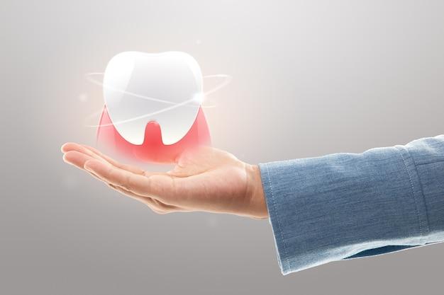Рука дантиста держит белые зубы на светло-сером фоне