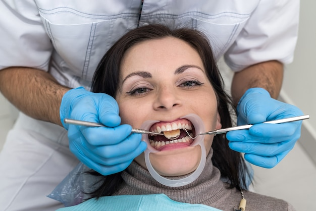 Dentist hands with instruments and patient face closeup