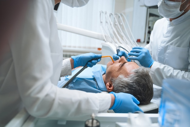 Dentist and his assistant are treating man in dental chair and giving him root canal