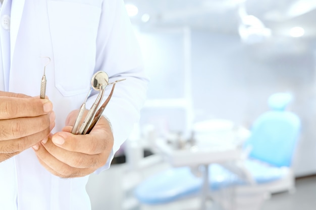 Dentist hold tools in his hand prepare to work in the room.