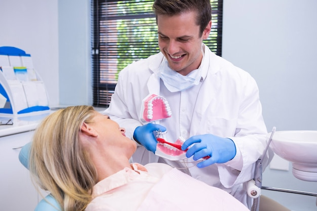 Dentist holding dental mould by woman at clinic