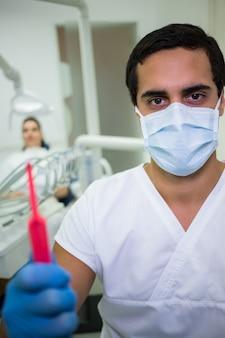 Dentist holding dental tools in dental clinic