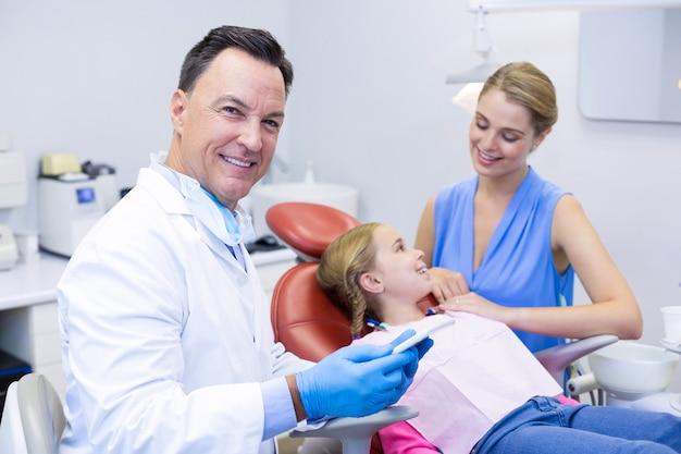Стоматолог держит цифровой планшет в стоматологической клинике