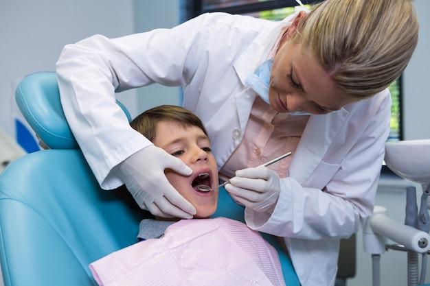 少年を診察しながら機器を保持している歯科医