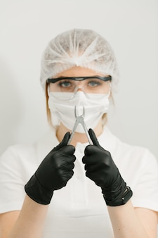 Dentist holding extracted tooth in dental clinic with black gloves
