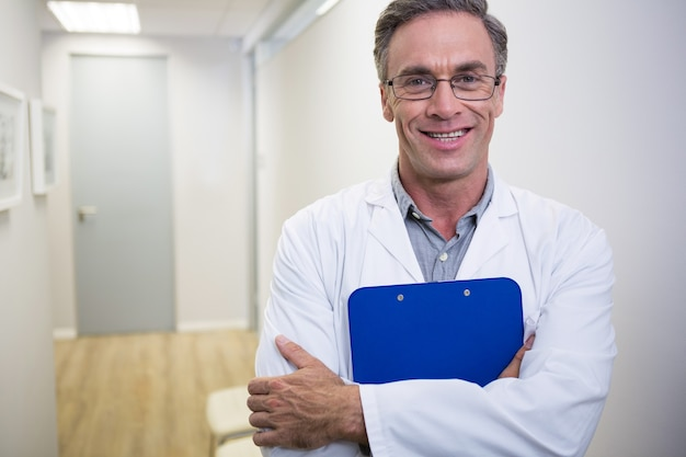 Dentist holding file while standing at lobby in dental clinic