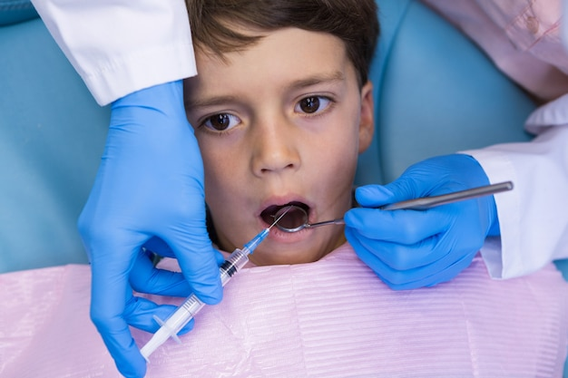 少年を診察しながら医療機器を保持している歯科医