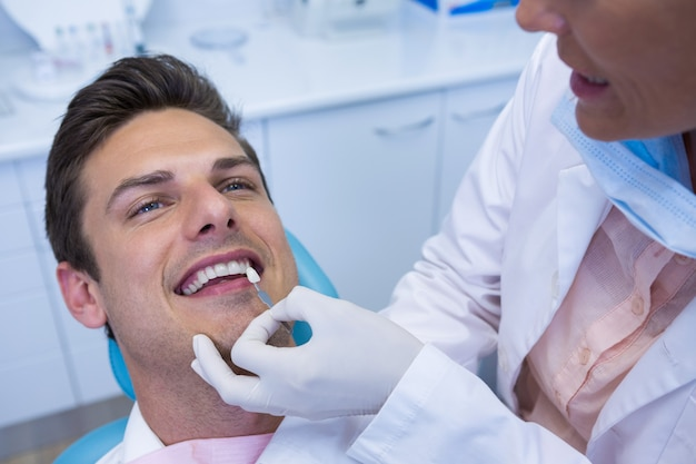 Dentist holding medical equipment while examining patient at medical clinic