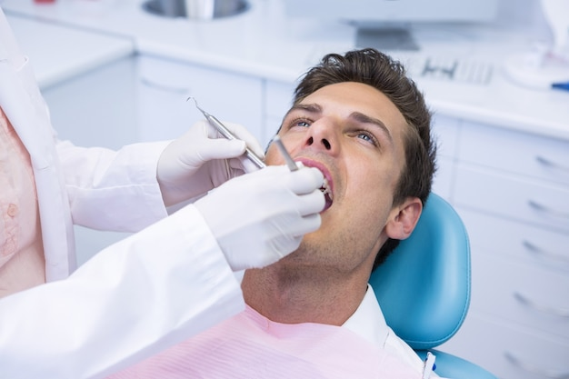 Dentist holding medical equipment while giving treatment to man