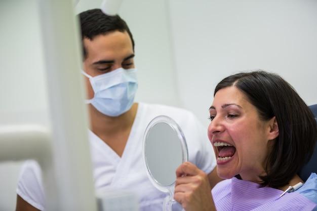 Dentista che tiene specchio davanti al paziente