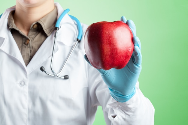 Dentist holding a ripe apple