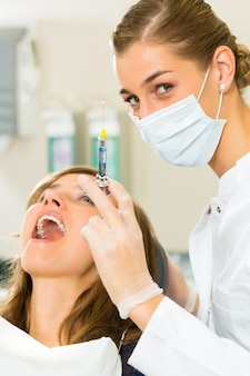 Dentist holding a syringe and anesthetizing her patient