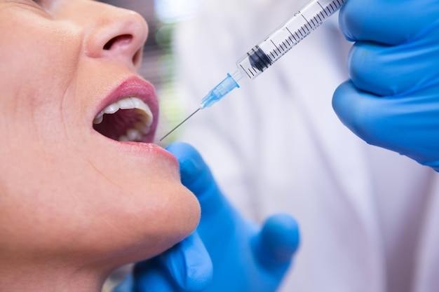 Dentist holding syringe by patient at medical clinic