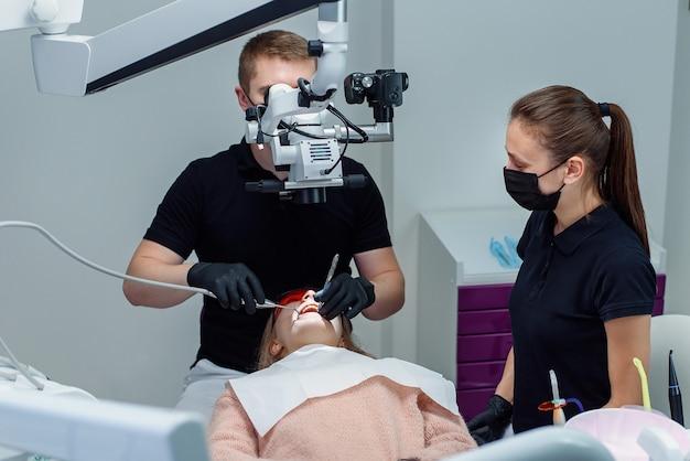 黒のラテックス手袋をはめた歯科医が歯科用顕微鏡を見て、女性患者の歯を