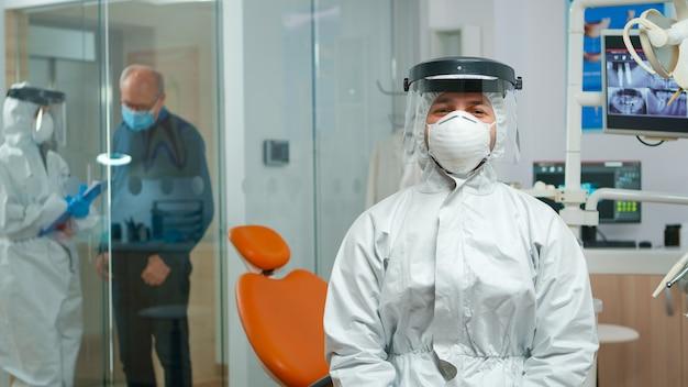 전염병 코로나바이러스 동안 구강 클리닉에 앉아 있는 카메라를 보고 웃고 있는 작업복을 입은 치과 의사. 보호복, 안면 보호대, 마스크, 장갑을 끼고 화상 통화를 하는 교정.