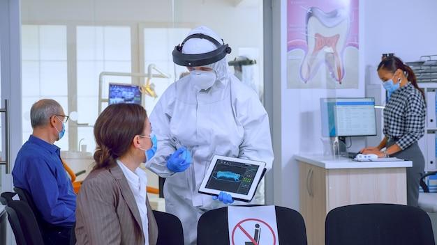 코로나바이러스 동안 치과 진료실에서 환자에게 치과 엑스레이를 설명하는 태블릿을 사용하는 작업복을 입은 치과 의사. 얼굴 가리개를 쓴 간호사, 디지털 장치를 사용하여 여성에게 방사선 사진을 보여주는 마스크