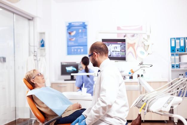 白衣を着た年配の女性に診断を言う歯科医院の歯科医。診察中に椅子に座っている患者と話している医療歯の世話人。