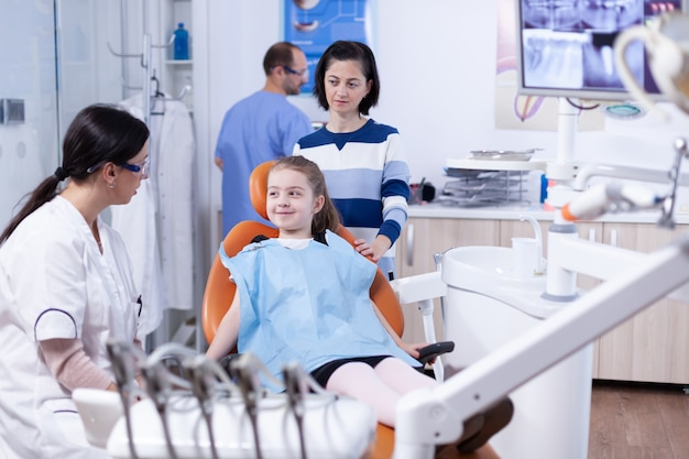 小さな女の子に治療は苦痛ではないと言っている歯科医院の歯科医。歯の間に母親と一緒にいる子供は、椅子に座っている口内検査で診察します。