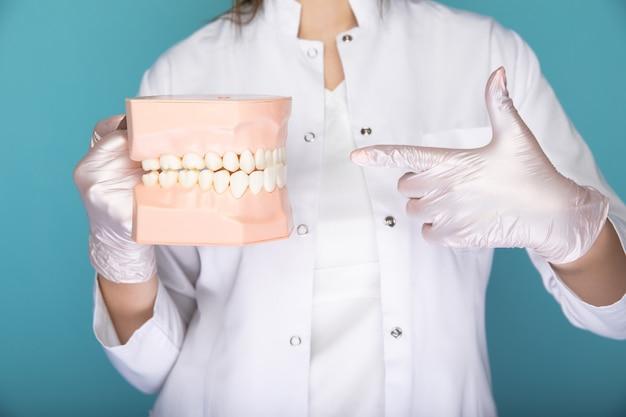 파란색 스튜디오에서 격리된 의료 물건을 들고 장갑을 낀 치과 의사.