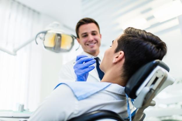 彼のオフィスの歯科医は彼の患者の歯を検査する準備ができています。