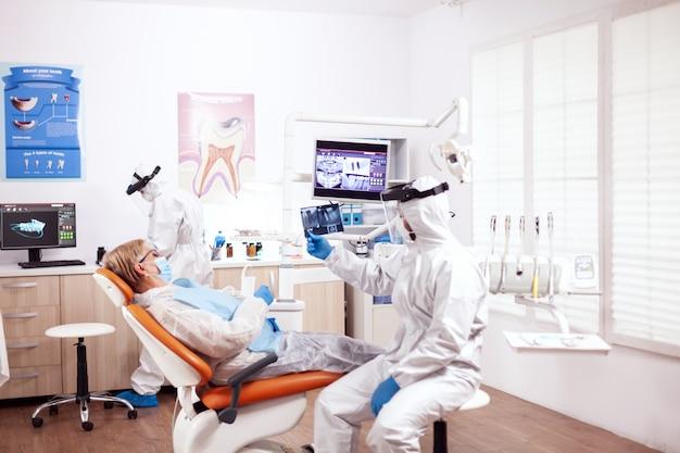 椅子に座って患者のx線写真を保持している保護具アガシントコロアンウイルスの歯科医。歯科医院での診察中に防護服を着た年配の女性。