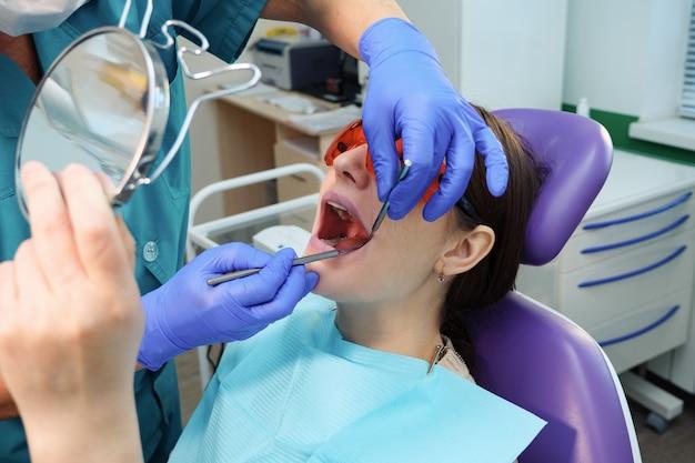 制服を着た歯科医は、治療後、鏡の中の歯を歯科用椅子に座っている若い女性に見せています。