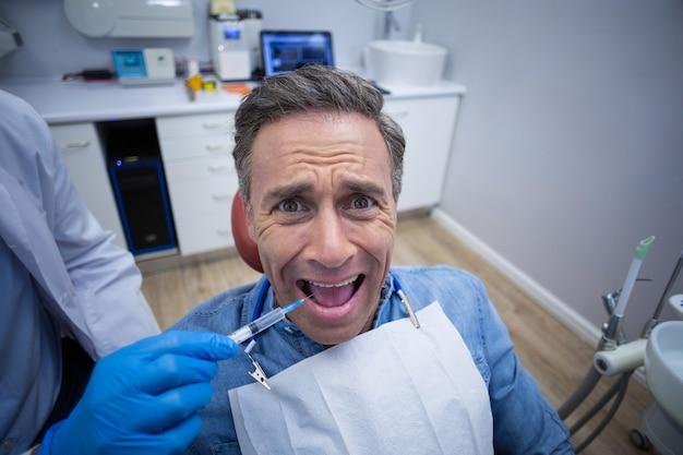 怖がる男性患者の口に麻酔薬を注入する歯科医