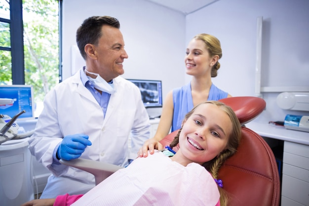Dentist interacting with young patient and her mother