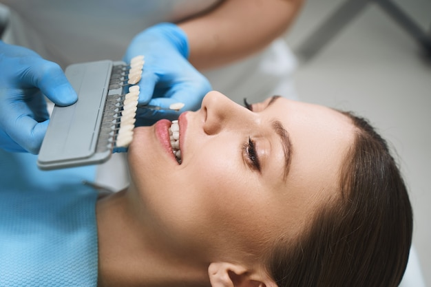 Dentist is helping young female patient in chair with choosing colour before getting veneers