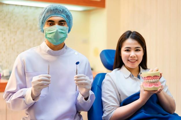 歯科医はモデルの歯を手に持っています。