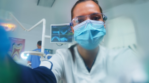 Dentist leaning over patient putting oxigen mask before surgery in stomatological office. doctor working in modern orthodontic clinic wearing protection mask and gloves during heatlhcare checking