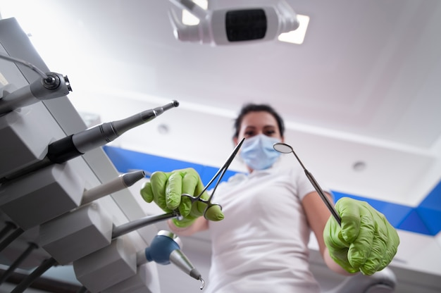 Dentist looking down holding tools in hand and standing near a dental equipment