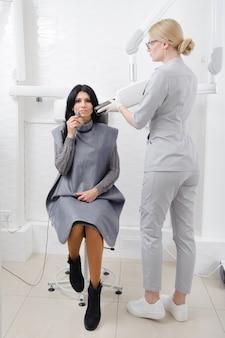 치과 의사는 치과에서 여성을위한 턱 엑스레이 이미지를 만듭니다.
