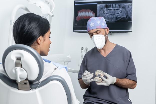 Стоматолог дает объяснения пациенту, держа в руках пластиковую зубную форму в стоматологической клинике