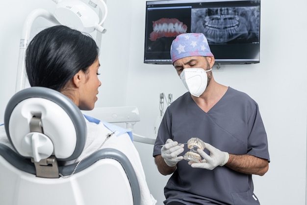 Dentist making a explanation to a patient while holding a plastic dental mould in a dental clinic