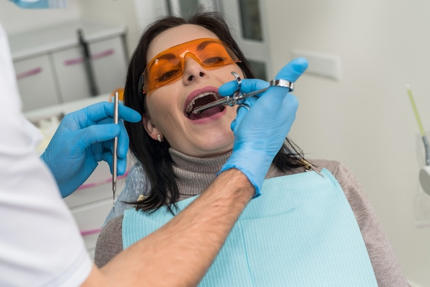 Dentist making injection of anesthetic to patient